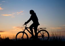 Biker silhouette against sunset Stock Photo