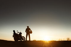 Biker& x27 ; silhouette de s avec le coucher du soleil de moto image stock