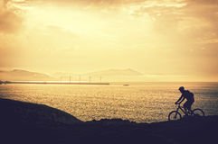 Biker silhouette riding Stock Photography