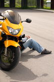 Biker Sitting On The Ground. A biker sitting on the ground beside his motorcycle Stock Photo
