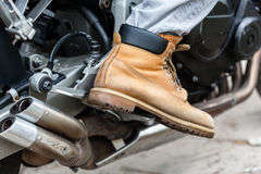 Biker sitting on motorcycle, close-up view on legs. Stock Images