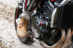 Biker sitting on motorcycle, close-up view on legs. Stock Photos