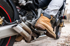 Biker sitting on motorcycle, close-up view on legs. Stock Photo