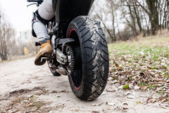 Biker sitting on motorcycle, close-up view on rear wheel Royalty Free Stock Photography