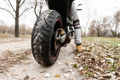 Biker sitting on motorcycle, close-up view on rear wheel Royalty Free Stock Photo