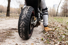 Biker sitting on motorcycle, close-up view on rear wheel. Royalty Free Stock Photos