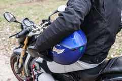 Biker sitting on motorcycle, holding his blue helmet. Royalty Free Stock Photography