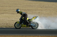 Biker with smoking tires. Motorcycle stunt rider spinning and smoking tires Royalty Free Stock Images