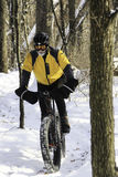 Biker in snowy forest on single track Stock Images