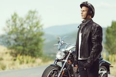 Biker standing in front of a motorcycle Stock Images