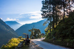 Biker is standing on Himalayas mountain road. Himalayas landscape in the morning Stock Photography