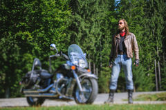 Biker standing by his custom made cruiser motorcycle. Handsome biker with long hair and beard standing near his custom made cruiser motorcycle. Biker is wearing Stock Photos