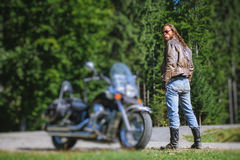 Biker standing by his custom made cruiser motorcycle. Handsome man with long hair and beard standing near his custom made cruiser motorcycle. Biker is wearing Stock Images
