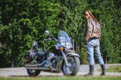 Biker standing by his custom made cruiser motorcycle. Handsome man with long hair and beard standing near his custom made cruiser motorcycle. Biker is wearing Stock Photos