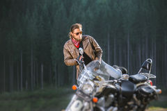 Biker standing by his custom made cruiser motorcycle. Handsome young biker is sitting down on his long distance travel motorbike with forest on the background Stock Image