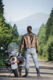 Biker standing by his custom made cruiser motorcycle Stock Image