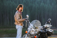 Biker standing by his custom made cruiser motorcycle. Long haired biker standing near his custom made cruiser motorcycle, wearing leather jacket and blue jeans Stock Photography