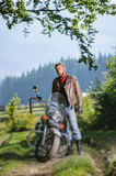 Biker standing by his custom made cruiser motorcycle. Young handsome serious man standing by his custom made cruiser motorcycle on a sunny day with forest on the Stock Photos