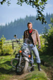 Biker standing by his custom made cruiser motorcycle. Young handsome biker standing by his custom made cruiser motorcycle on a sunny day with forest on the Stock Photo