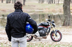 Biker standing near motorcycle holding his blue helmet. Royalty Free Stock Photography