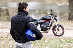 Biker standing near motorcycle holding his blue helmet. Stock Photo