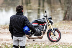 Biker standing near motorcycle, holding his blue helmet. Stock Image
