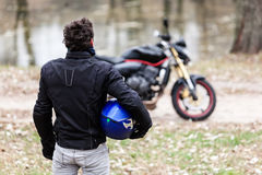 Biker standing near motorcycle, holding his blue helmet. Royalty Free Stock Photo