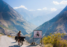 Biker is standing near road sign on Himalayas mountain road. Manali-Leh road in Indian Himalayas, Jammu and Kashmir State, North India Stock Photography
