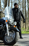 Biker stands near his bike Royalty Free Stock Photo