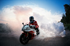 Biker staying on bike  road with smoke of the tire, burn out in the moto show.  the Sunset Royalty Free Stock Photo
