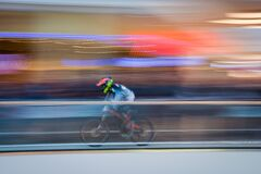 Biker streaking past blurred background Stock Photo
