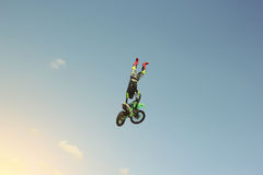 Biker stuntman doing a stunt in the air. Extreme sport Stock Photo