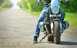 Biker in stylish outfit sits on his motorcycle. royalty free stock image