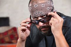 Biker in Sunglasses and Bandanna. Intimidating male biker in bandana looking over his sunglasses Stock Photos