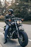 Biker in sunglasses and leather jacket on the road Royalty Free Stock Photo