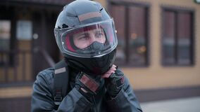 Biker takes off his black helmet in the parking lot, arriving at the destination