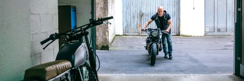 Biker taking motorbike to the garage. Front view of biker taking custom motorbike to the garage stock image