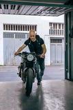 Biker taking motorbike to the garage. Front view of biker taking custom motorbike to the garage royalty free stock images