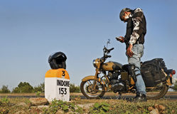 Biker texting sms using mobile phone Stock Image