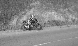 Biker theme: beautiful woman with body posing with motorbik Stock Photos