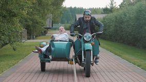 Biker with tie ride motorcycle with woman nurse costume grimacing in sidecar stock video footage