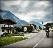 Biker touring Europe. Biker on the road in Alps, extreme sport, moto tour along European mountains, beautiful landscape, travel and tourism concept Royalty Free Stock Photos
