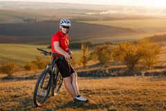 Biker tourist travel on mountain bike. Autumn landscape. Sportsman on bicycle in red jersey and white helmet Royalty Free Stock Photography