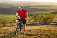 Biker tourist travel on mountain bike. Autumn landscape. Sportsman on bicycle in red jersey and white helmet Royalty Free Stock Image