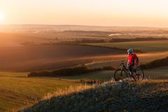 Biker tourist travel on mountain bike. Autumn landscape. Sportsman on bicycle in red jersey and white helmet Royalty Free Stock Photo
