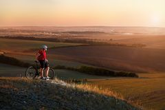Biker tourist travel on mountain bike. Autumn landscape. Sportsman on bicycle in red jersey and white helmet Royalty Free Stock Images