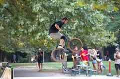 Biker tricks in skate park. Extreme bicycle rider performing freestyle tricks on his bike in city park,Varna Bulgaria Royalty Free Stock Photo