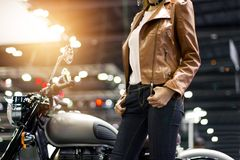 Biker woman in brown leather jacket with a motorcycle. Biker woman in a brown leather jacket with a motorcycle on street background Stock Photography