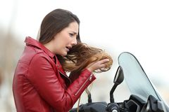 Biker woman complaining about tangled hair. Portrait of a sad biker woman complaining about tangled hair after a motorkike travel Royalty Free Stock Images