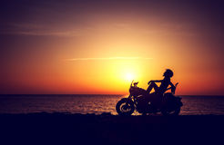Biker woman resting outdoors. Silhouette of a biker woman resting on the beach on sunset background, enjoying freedom and active lifestyle, having fun in a Royalty Free Stock Photos